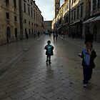 Child wandering along Stradun, Dubrovnik, Croatia by Sheldon Levis