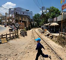 Child jumping railway tracks. Trai Mat, Da Lat (Dalat), Vietnam by Sheldon Levis
