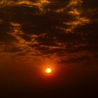 burning sun through clouds by bharatrawail