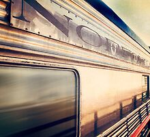 Silver train speeding past. by Jennifer Westmoreland