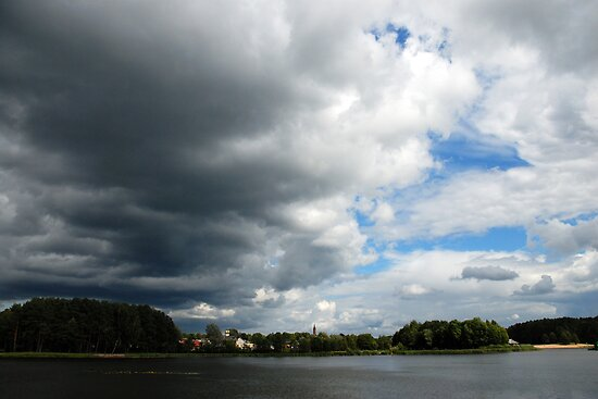 Clouds, lake and town by Antanas