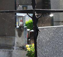 Spider webs in the sun on gravesite crucifix - Innsbruck, Austria by tracyannjones