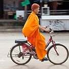 Novice monk cycling, Vang Vieng, Laos by John Spies