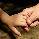 Mother holding baby daughter's (2-4) hand by Sami Sarkis
