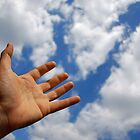 Mans hand reaching for clouds by Sami Sarkis