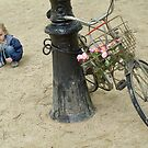 Girl playing with sand near bicycle by Sami Sarkis