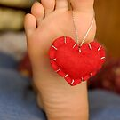 Valentine heart hanging on girl&#x27;s barefeet by Sami Sarkis