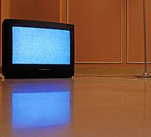 Television displaying static reflected in floor by Sami Sarkis