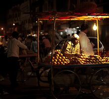 A shopkeeper selling fruits in the night market by Neha Singh