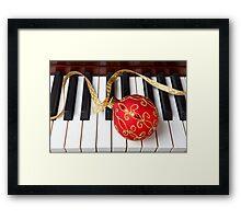 Christmas ornament on piano keys Framed Print