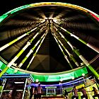 A colourful ferris wheel at night by efecreata