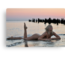 Lovely blond naked model lying on sunset beach at dramatic sunset  Canvas Print