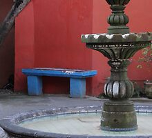 The Blue Bench, The Red Wall And A Green Fountain - El Banco Azul, El Muro Rojo Y Una Fontana Verde by Bernhard Matejka