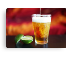 Beer being poured into glass with lime Canvas Print