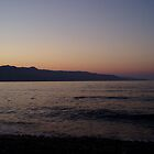 Orange pink sunset over sea in Crete with lilac mountains by Grace Johnson