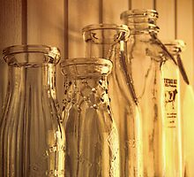 Old milk bottles on shelf by Sandra Cunningham