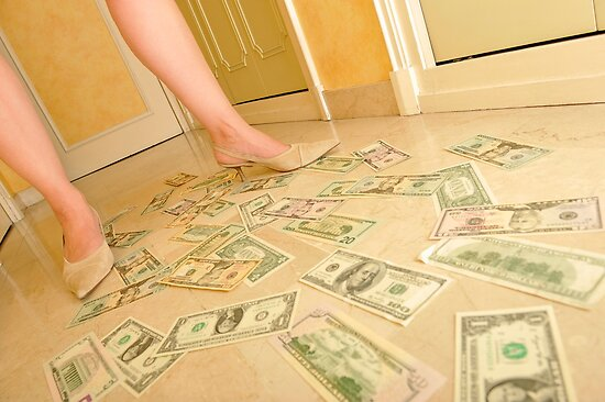 Woman's legs walking on Us dollars banknotes on floor. by Sami Sarkis