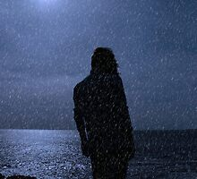 silhouette of lone woman on cliff edge during rain shower by morrbyte