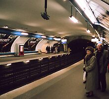 Couple waiting at the subway, paris. by Miquel  Gil