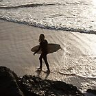 Surfer walking on beach at sunset by Pat Garret