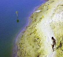 Man walking along river bank(Ganga) in India. by wehavegrown