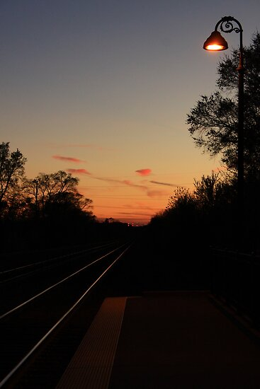 The Sun setting on Lisle, IL train tracks leaving the station. by Adam Kuehl