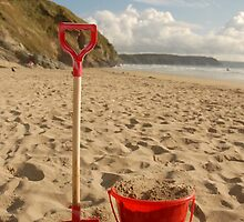 Red bucket and spade in the sand on the beach by katbphotography