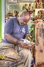 Bahamian Sculptor carving the Wood by 242Digital
