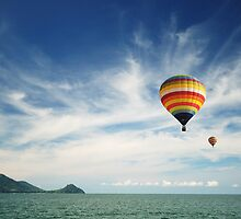 Colorful hot air balloon flying over the sea by goldsaintphoto