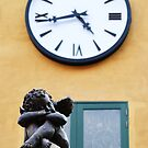 Statue of little cupid under the clock by goldsaintphoto