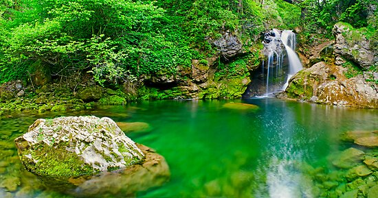 Beatiful waterfall falling into peaceful river by nrasic