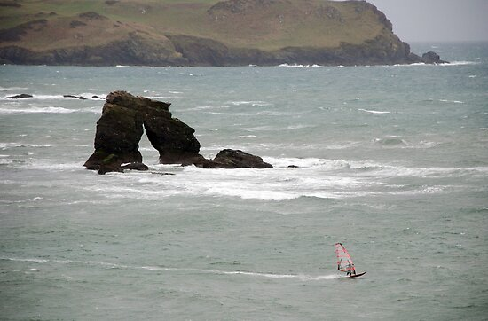 Windsurfer in stormy weather passes Thurlestone Rock, Devon, UK by silverportpics