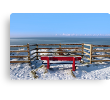 seasonal snow covered red bench sea view Canvas Print