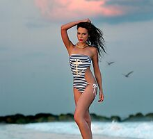 Beautiful brunette posing sexy at the tropical beach during sunset time by Anton Oparin