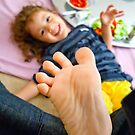 Little Girl Playing Footsie by Kuzeytac