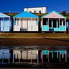 Beach huts reflected. by Karen  Betts