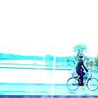 girl on bike on bridge over river by deThierry