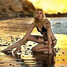 Sexy model posing at golden sunset at passific coast of California by Anton Oparin