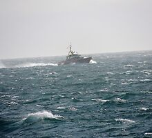 Small Boat in Stormy Waters by islandphotoguy