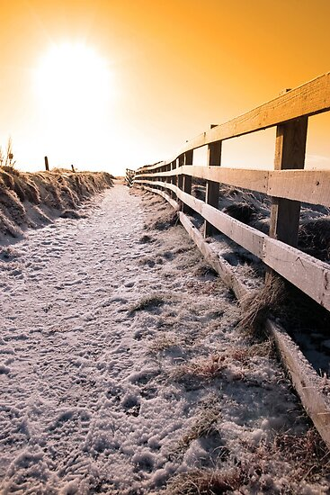 snow covered frozen path on cliff fenced walk at sunset by morrbyte
