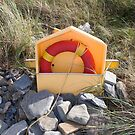 beach lifebuoy buried in the stones by morrbyte