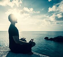Man Meditating At Sunset by visualspectrum