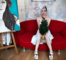 Young woman in a white dress sitting on a red lips couch and holding a small Christmas tree  by Reinvention