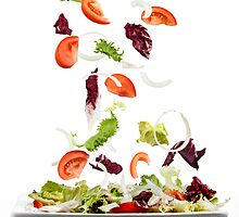 Salad with fresh vegetables falling on plate by paulrommer