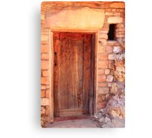 Old wooden door and stone house Canvas Print