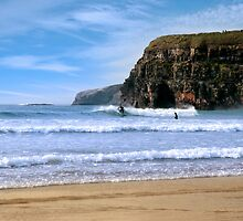 surfers surfing near ballybunion cliffs by morrbyte