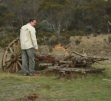 Man standing over wooden wagon relics by mountainshack08