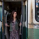 Woman standing in the doorway of a derelict bus by Ben Ryan