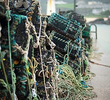 Lobster pots stacked on the shore by photoeverywhere