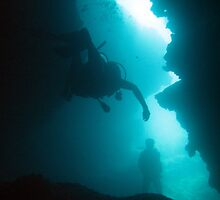Divers in an underwater cave by photoeverywhere
